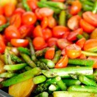 Grüner Spargel wird mit Tomaten und Kartoffeln in der Pfanne angebraten