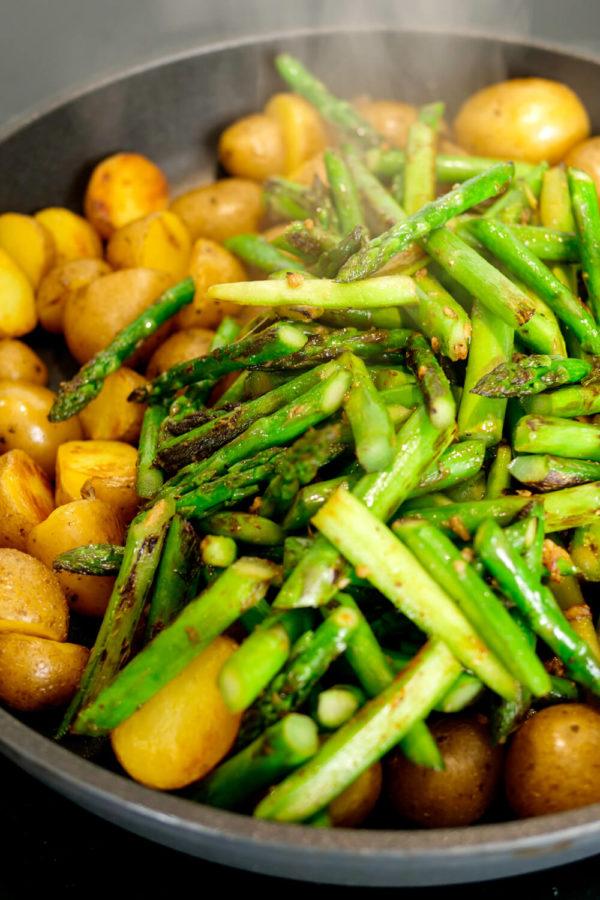Kartoffeln mit grünem Spargel in der Bratpfanne