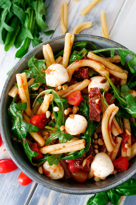 Italienischer Nudelsalat mit Pinienkernen, Mozzarella, Rucola und Tomaten in der Schüssel