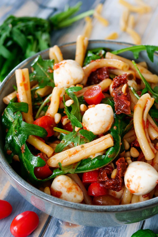 Italienischer Nudelsalat mit Rucola, Mozzarella, Tomaten und Pinienkernen in der grauen Schüssel