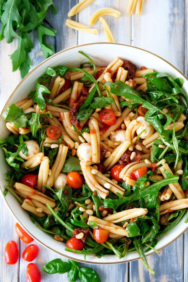 italienischer Nudelsalat mit Rucola, Tomaten, Mozzarella und Pinienkernen in der Schüssel