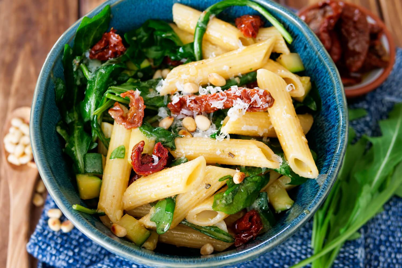 Nudelsalat mit Pinienkernen, getrockneten Tomaten, Rucola und Parmesan