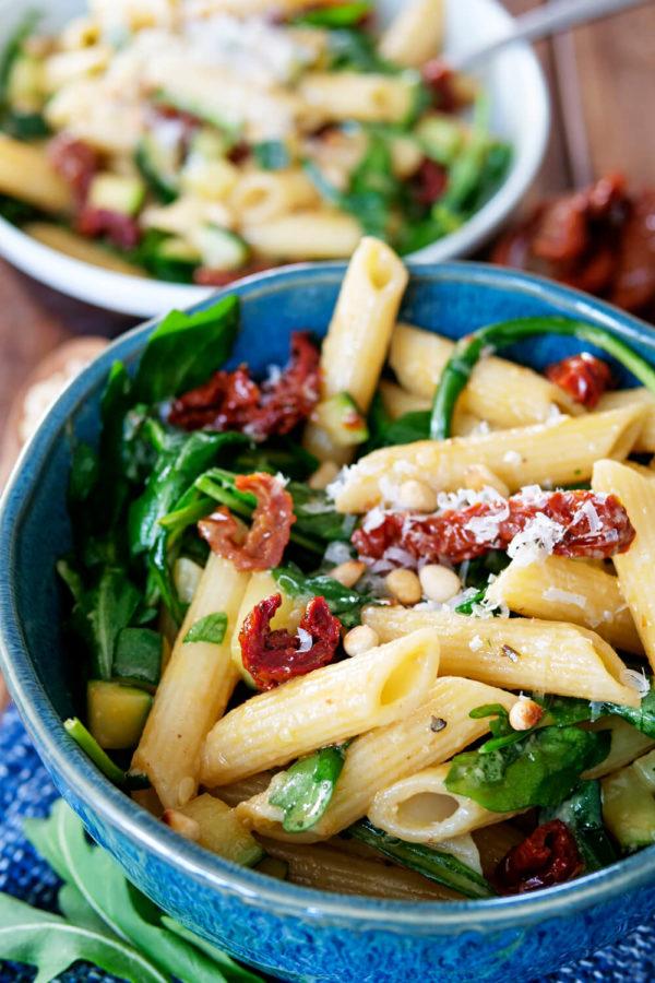Nudelsalat mit Rucola, getrockneten Tomaten, Pinienkernen und Parmesan in der Schüssel