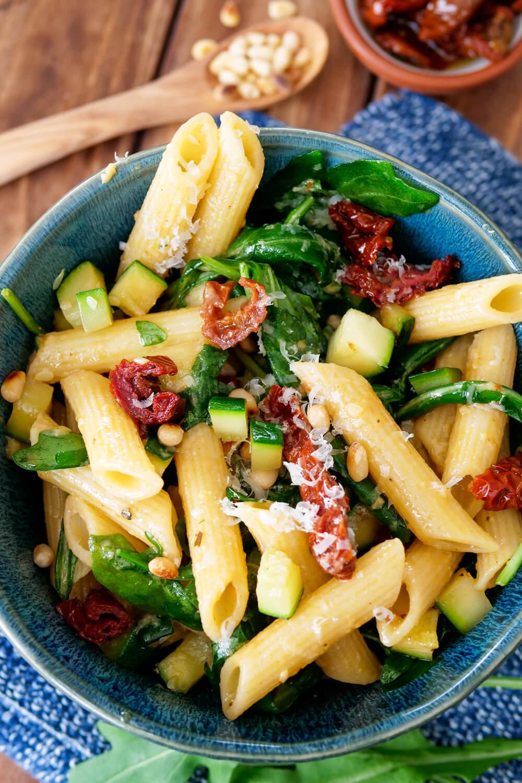 Nudelsalat mit Honig-Senf-Dressing, Rucola, getrockneten Tomaten, Pinienkernen und Zucchini
