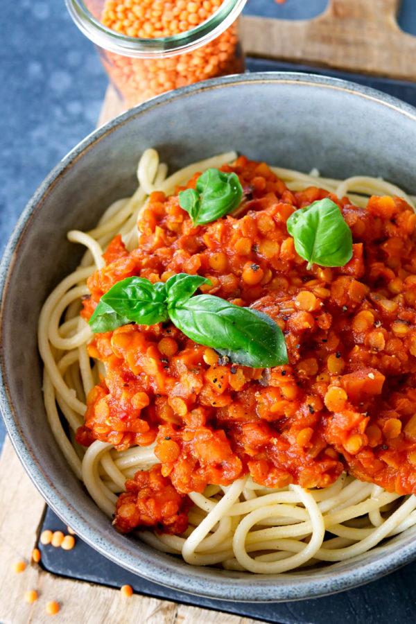 Spaghetti mit einer Bolognese aus roten Linsen mit Basilikum in der Schüssel