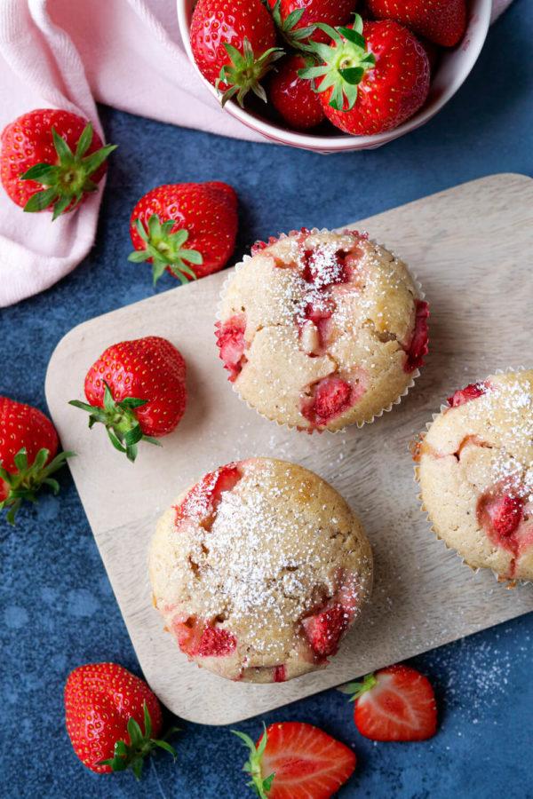Erdbeer-Muffins mit Dinkelmehl, frischen Erdbeeren und Puderzucker auf dem Holzbrett