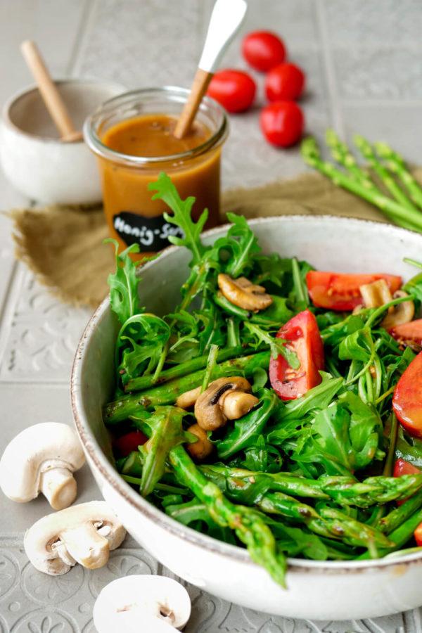Honig-Senf-Dressing im Glas und ein gemischter Salat mit Champignons, Spargel und Tomaten