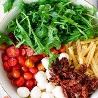 Rucola, Tomaten, Mozzarella, getrocknete Tomaten und Nudeln sind die Zutaten für den italienischen Nudelsalat