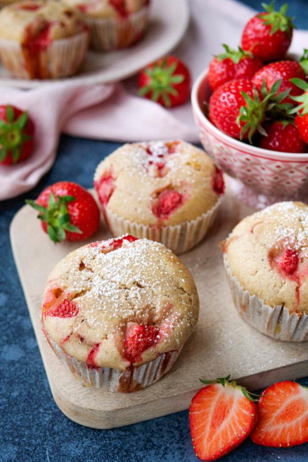 Gesunde Muffins mit Erdbeerfuellung und Puderzucker auf dem Holzbrett
