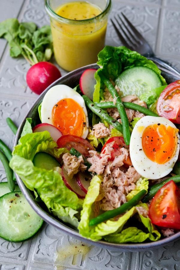 Nizza Salat mit Eiern, grünen Bohnen, Tomaten, Gurken, Radieschen und Dressing