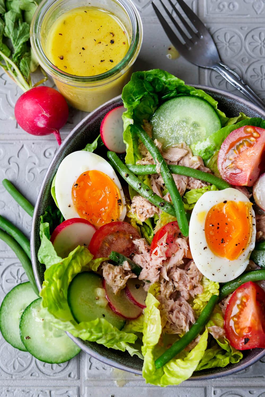 Bunter Nizza Salat mit gekochten Eiern, Thunfisch, Bohnen, Tomaten und Dressing