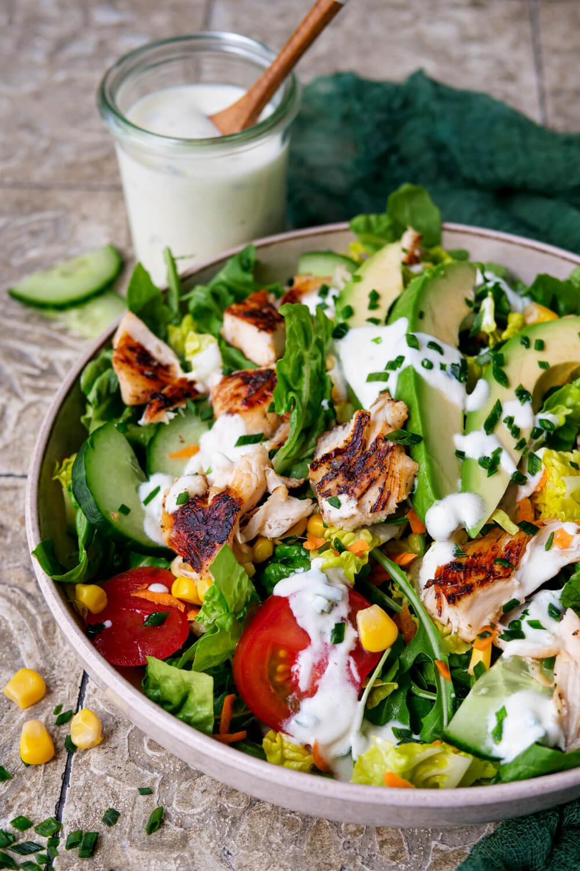 Salat mit Hähnchen, Tomaten, Mais, Gurken, Avocado und Joghurt-Dressing