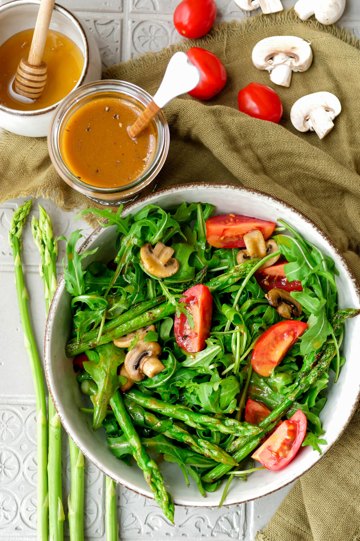 Gemischter Salat mit Champignons, Spargel und Tomaten und ein Dressing aus Honig und Senf im Glas