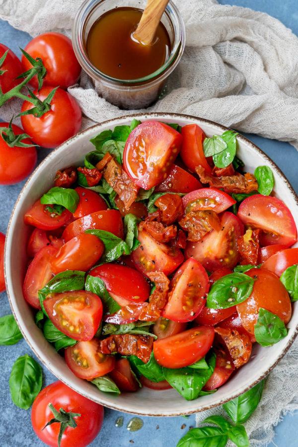 Einfacher Tomatensalat mit Tomaten, Basilikum, getrockneten Tomaten und einer Balsamico Vinaigrette