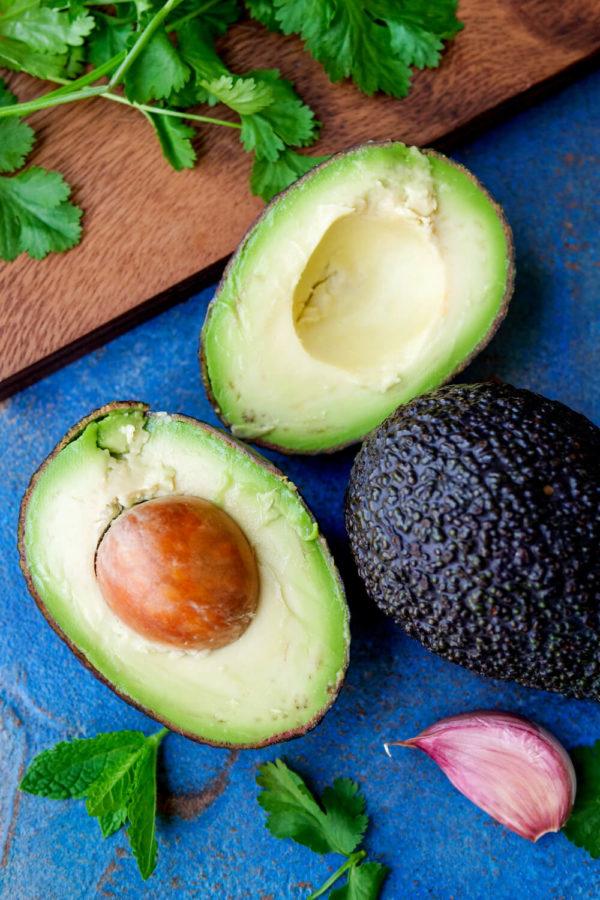 Halbierte Avocado mit Kern zu Knoblauch und Koriander