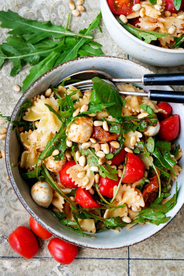 Aromatischer italienischer Nudelsalat mit Tomaten, Rucola, Pinienkernen und Mozzarella