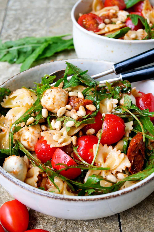 Einfacher italienischer Nudelsalat mit Tomaten, Rucola, Pinienkernen und Mozzarella