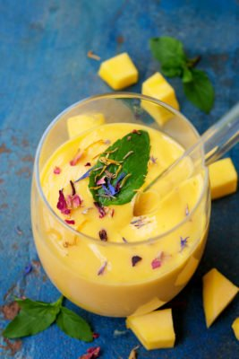 Mango Lassi mit frischer Minze und essbaren Blüten im Glas