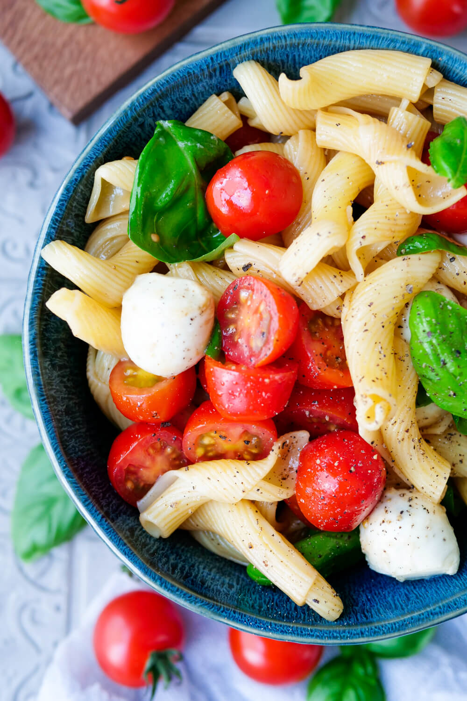 Einfacher Nudelsalat Caprese mit knackigen Tomaten, Basilikumblättern und Mozzarellakugeln