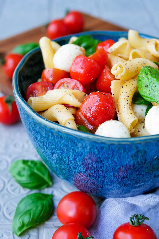 Nudelsalat Tomate-Mozzarella mit Basilikum in der blauen Schüssel