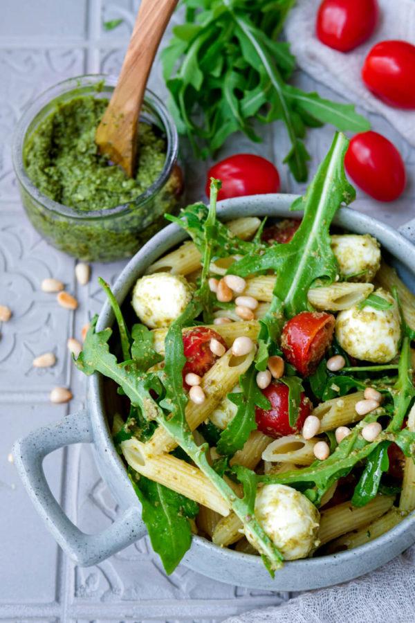 Nudelsalat mit Pesto, Rucola, Pinienkernen, Tomaten und Mozzarella in der Schale