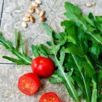 Frischer Rucola mit Tomaten und Pinienkernen