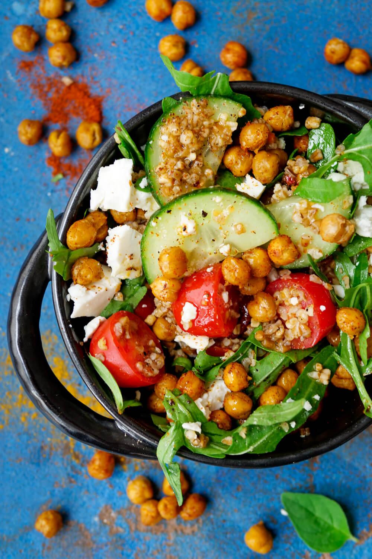 Salat mit Kichererbsen, Rucola, Getreide, Tomaten, Kichererbsen und Feta