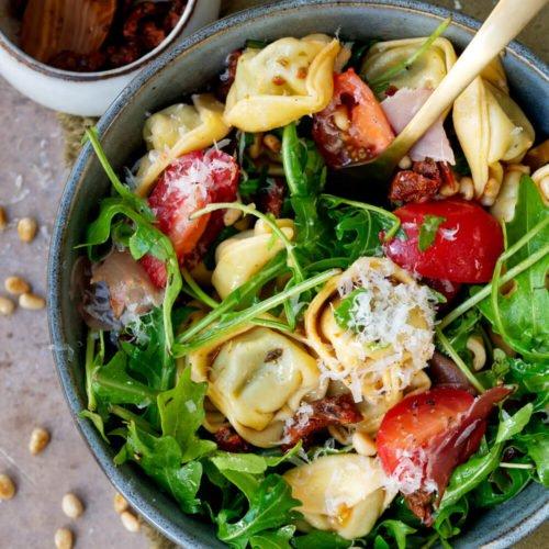 Tortellinisalat Rezept mit Parmesan, getrockneten Tomaten, Schinken, Rucola und Pinienkernen