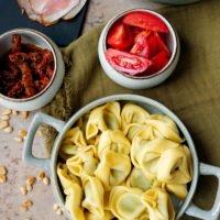 Tortellinisalat mit Serranoschinken, Tomaten, getrockneten Tomaten und Rucola
