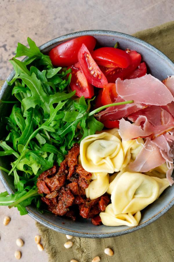 Rucola, getrocknete Tomaten, Tomaten, Schinken und Pinienkerne in der Schüssel
