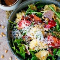 Einfacher Tortellinisalat mit Rucola, Tomaten, Schinken und Pinienkernen