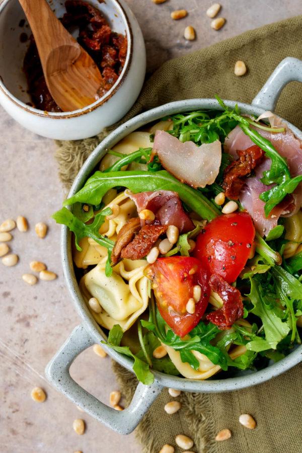 Tortellinisalat mit getrockneten Tomaten, Schinken und Rucola