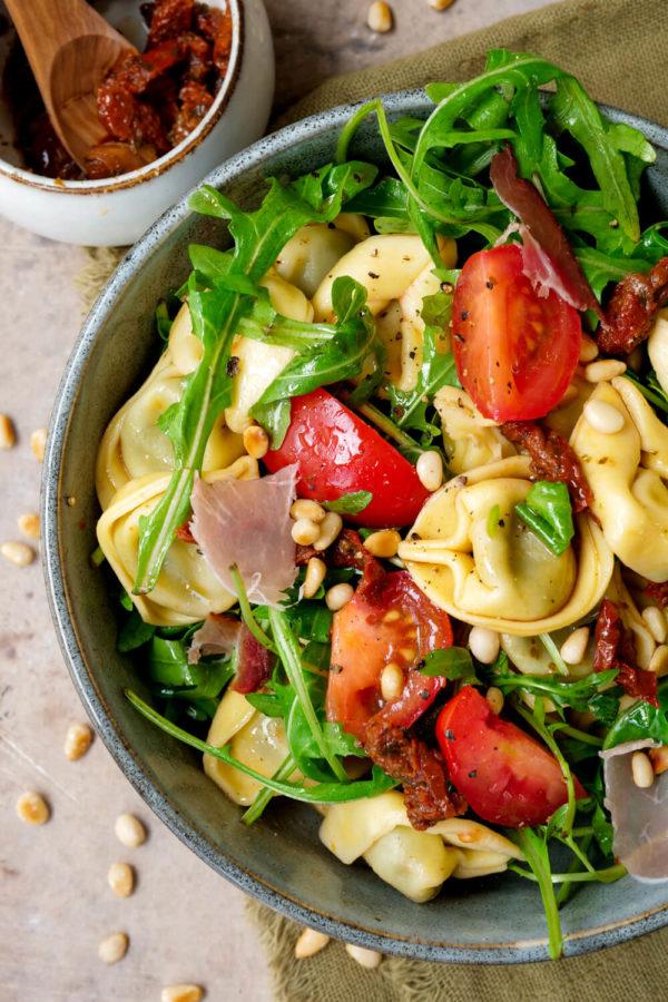 Leichter Tortellinisalat mit Essig, Öl, Tomaten und Rucola