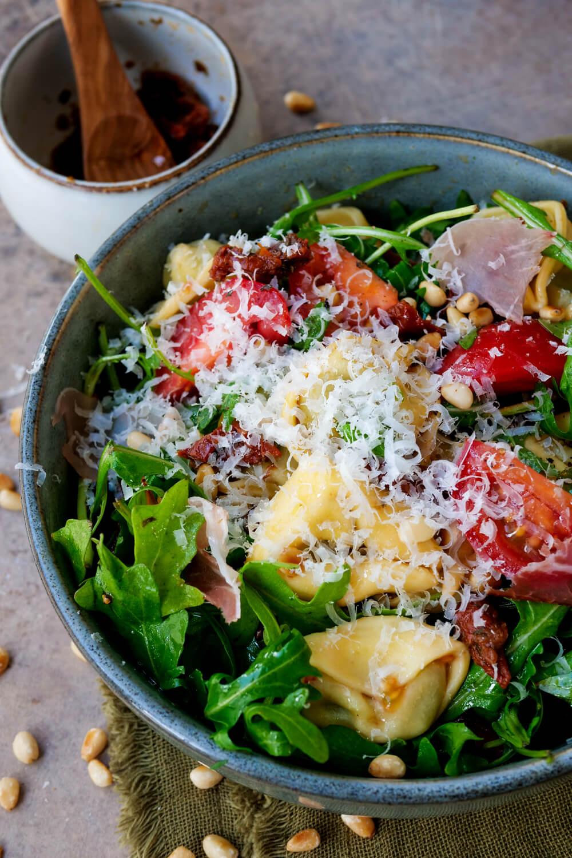 Mediterraner Tortellinisalat mit Schinken, Rucola, Tomaten, getrockneten Tomaten und Pinienkernen