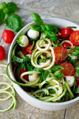Roher Zucchinisalat mit Tomaten, Mozzarella und Basilikum in der Schüssel