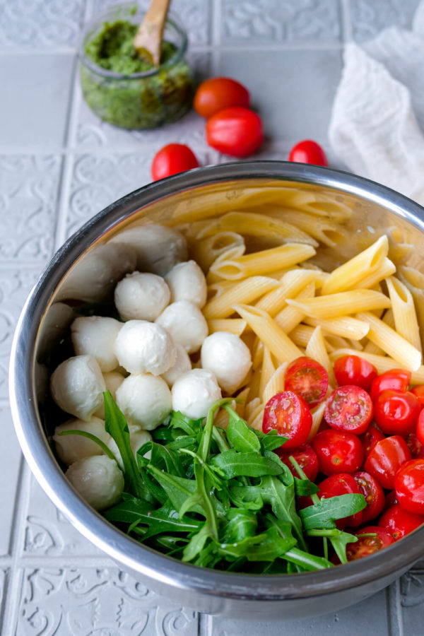 Nudeln, Mozzarella, Rucola und Tomaten in der Schüssel für den Nudelsalat