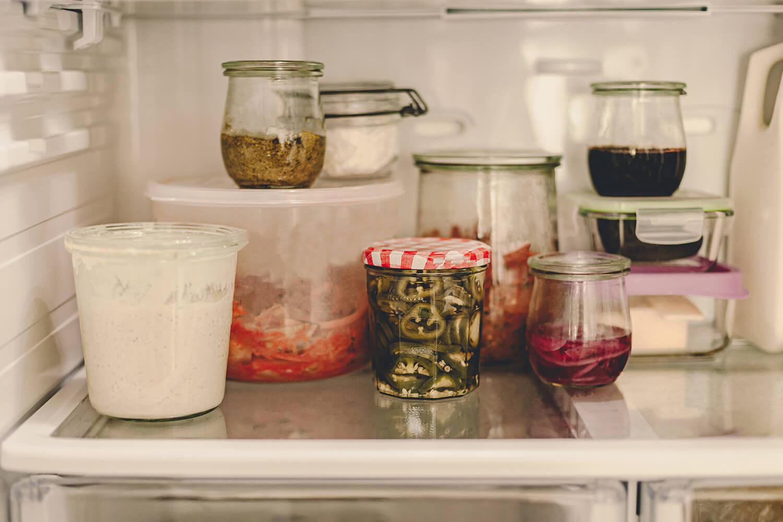 Verschiedene Gläser mit Vorräten im Kühlschrank