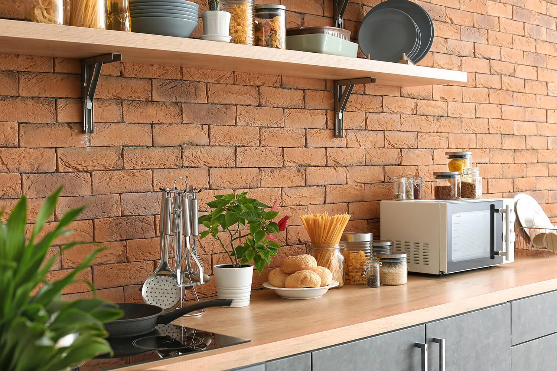 Lebensmittel für den Vorrat auf Regal in Küchenzeile mit Backsteinwand