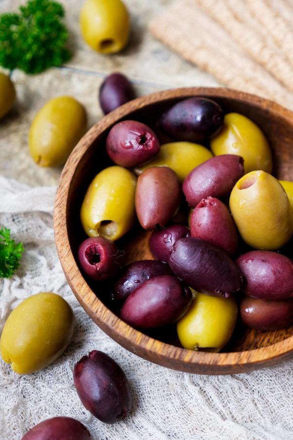 Grüne Oliven mit Kalamata Oliven in der Holzschale