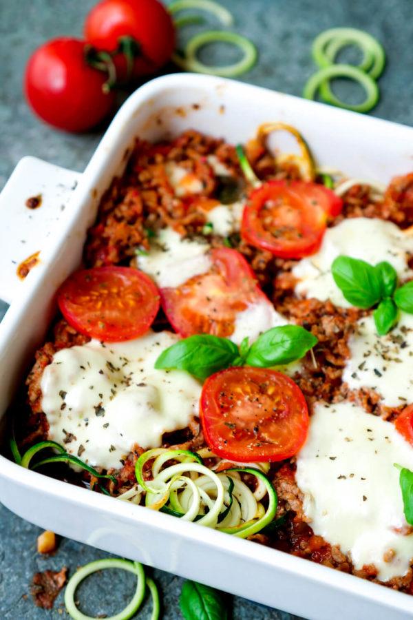 Zucchiniauflauf mit Hackfleisch, Tomatenscheiben und Mozzarella in der Auflaufform