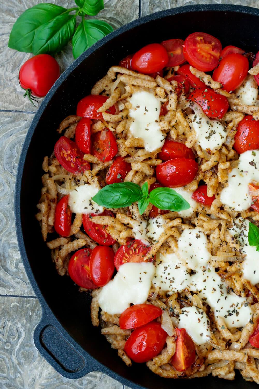 Spätzlepfanne mit halbierten Tomaten, Mozzarella und Basilikum