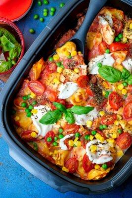 Vegetarischer Tortelliniauflauf mit Tomaten, Mais, Erbsen und Mozzarella
