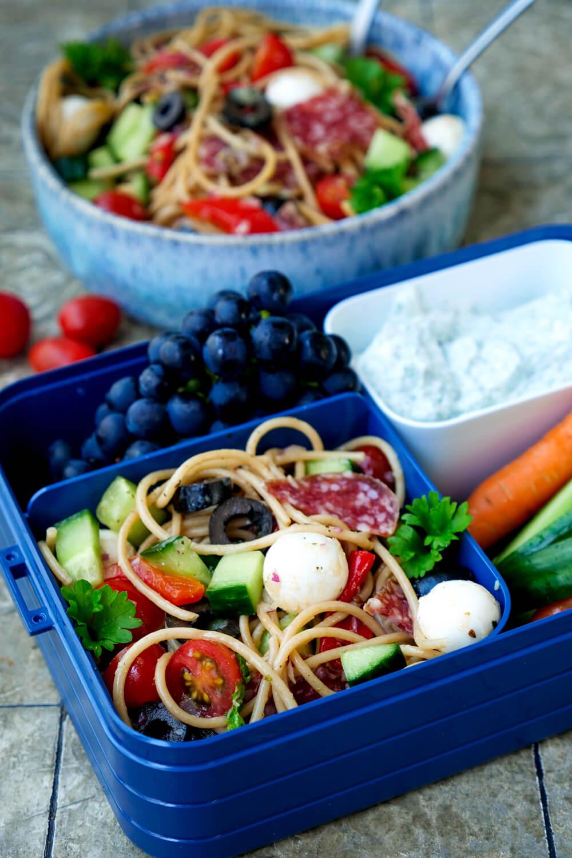 Bentobox-Salat mit Vollkornnudeln, Salami, Oliven und Gurke