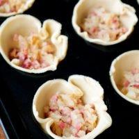 Blätterteig in Muffinform mit Speck und Zwiebeln füllen