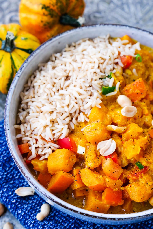 Kürbis-Curry mit Kokosmilch, Paprika, Reis, Erdnüssen und Frühlingszwiebeln