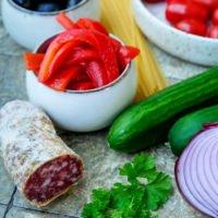 Zutaten für den Spaghetti-Salat: Gegrillte Paprika, Oliven, Tomaten, Gurke, Zwiebel, Salami und Spaghetti
