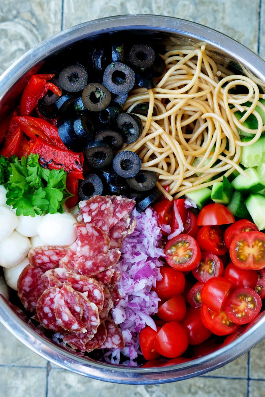 Spaghetti, Oliven, gegrillte Paprika, Mozzarella, Salami, Zwiebeln, Tomaten und Gurke in der Schüssel