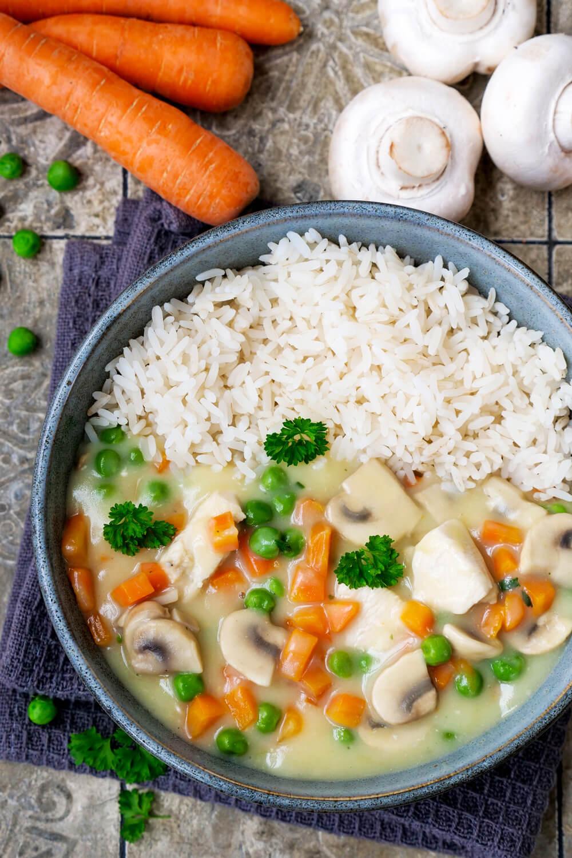 Klassisches Hühnerfrikassee mit Hähnchen, Gemüse und Reis