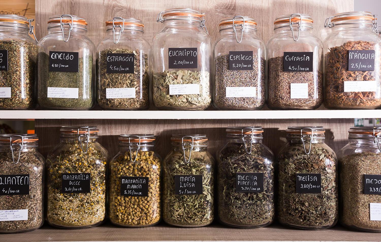Verschließbare Gläser mit getrockneten Kräutern in Küchenregal